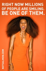 Sexy young African American adult woman with big hair wearing dress on orange background laughing.